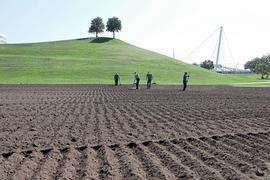 Rekultivierung unterhalb des grüngebliebenen Festhügels: Aufwendige Aufbereitungsarbeiten laufen in der Ebene, wo die Fest-Hauptbühne steht, damit auf dem braunen Feld wieder Gras wächst.