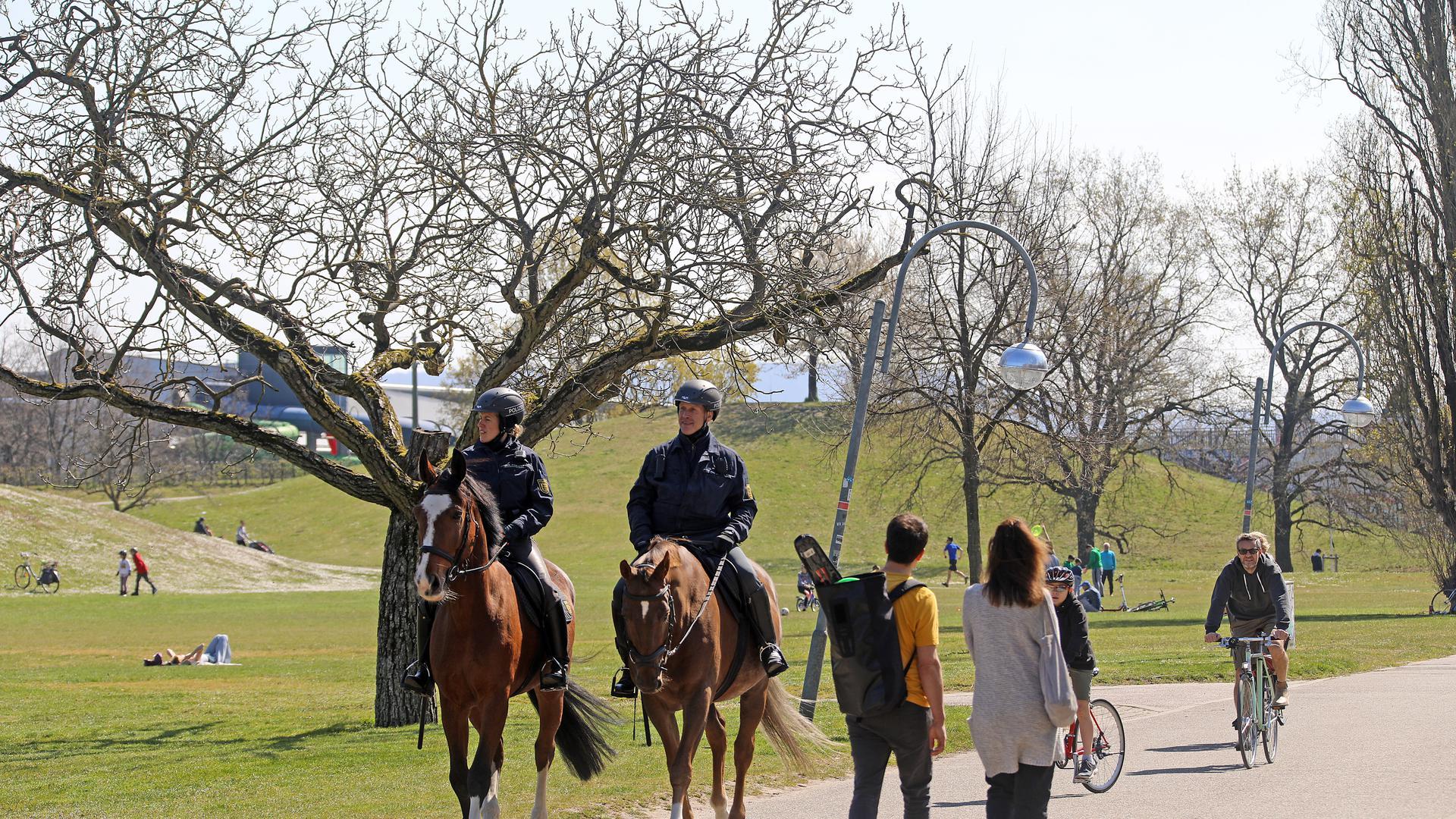 Ein Polizistenduo auf zwei großen Braunen patrouilliert am Samstagnachmittag in der Karlsruher Günther-Klotz-Anlage. Am Tag, an dem für viele Familien die Osterferien beginnen, gelten weiter strenge Bestimmungen zum Schutz vor Infektionen.