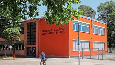 Amerikaner in Karlsruhe: In der Nordstadt weist vieles noch heute auf die Zeit hin, als US-Bürger das Viertel bewohnten. Während die Bekleidung des Radfahrers wohl Zufall ist, trägt die Elementary School ihren Namen aus gutem Grund.