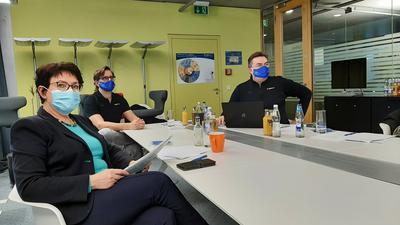 Drei Menschen mit Masken an einem großen weißen Tisch.