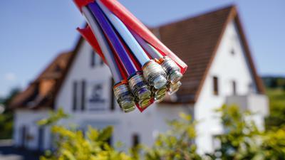 """Ein Bündel mit Umhüllungen für Glasfaserkabel hängt an einem Schild und vor einem Wohnhaus. (Zu dpa """"Fortschritte bei Breitbandausbau - aber große regionale Unterschiede"""") +++ dpa-Bildfunk +++"""