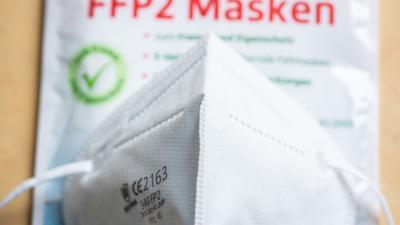 Eine FFP2-Maske liegt auf einem Tisch auf der Verkaufsverpackung. Zum Schutz vor dem Coronavirus sollen mehr Menschen aus Risikogruppen vom Bund finanzierte FFP2-Masken bekommen als zunächst vorgesehen. Nach einem Abgleich mit Versichertendaten der Krankenkassen sollen nun 34,1 Millionen statt 27 Millionen Bürger in diesen Tagen Gutscheine für zwölf FFP2-Masken zugesandt bekommen. +++ dpa-Bildfunk +++