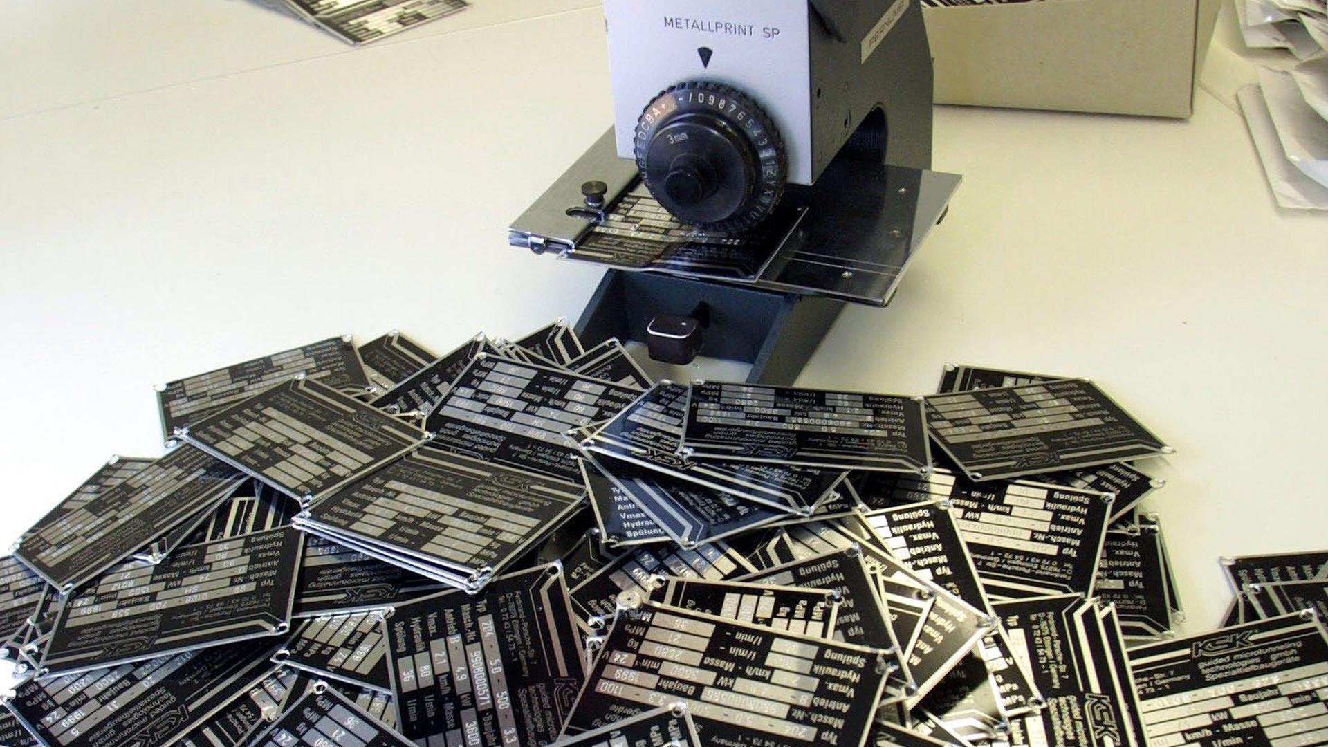 In der Landespolizeidirektion Karlsruhe werden eine Prägemaschine und Blanko-Typenschilder gezeigt, die im milliardenschweren FlowTex-Verfahren eine wichtige Rolle spielen (Archivfoto vom 06.09.2001). Nach jahrelangem Schweigen hat die Schlüsselfigur im milliardenschweren FlowTex-Schadenersatzprozess am Donnerstag (09.06.2005) in Karlsruhe ihr Schweigen gebrochen. Vor dem Landgericht wollte der 55 Jahre alte Betriebsprüfer im Laufe des Prozesses unter anderem Aussagen machen zur Rolle der Verwaltung im gigantischen FlowTex-Betrugssystem, das erst im Jahr 2000 aufgedeckt werden konnte. Dem aussagenden Finanzbeamten wird vorgeworfen, das betrügerische System mit nicht vorhandenen Bohrsystemen bereits bei einer Betriebsprüfung 1996 erkannt und gedeckt zu haben. Foto: Uli Deck dpa/lsw (zu dpa/lsw 7167 vom 09.06.2005) +++ dpa-Bildfunk +++