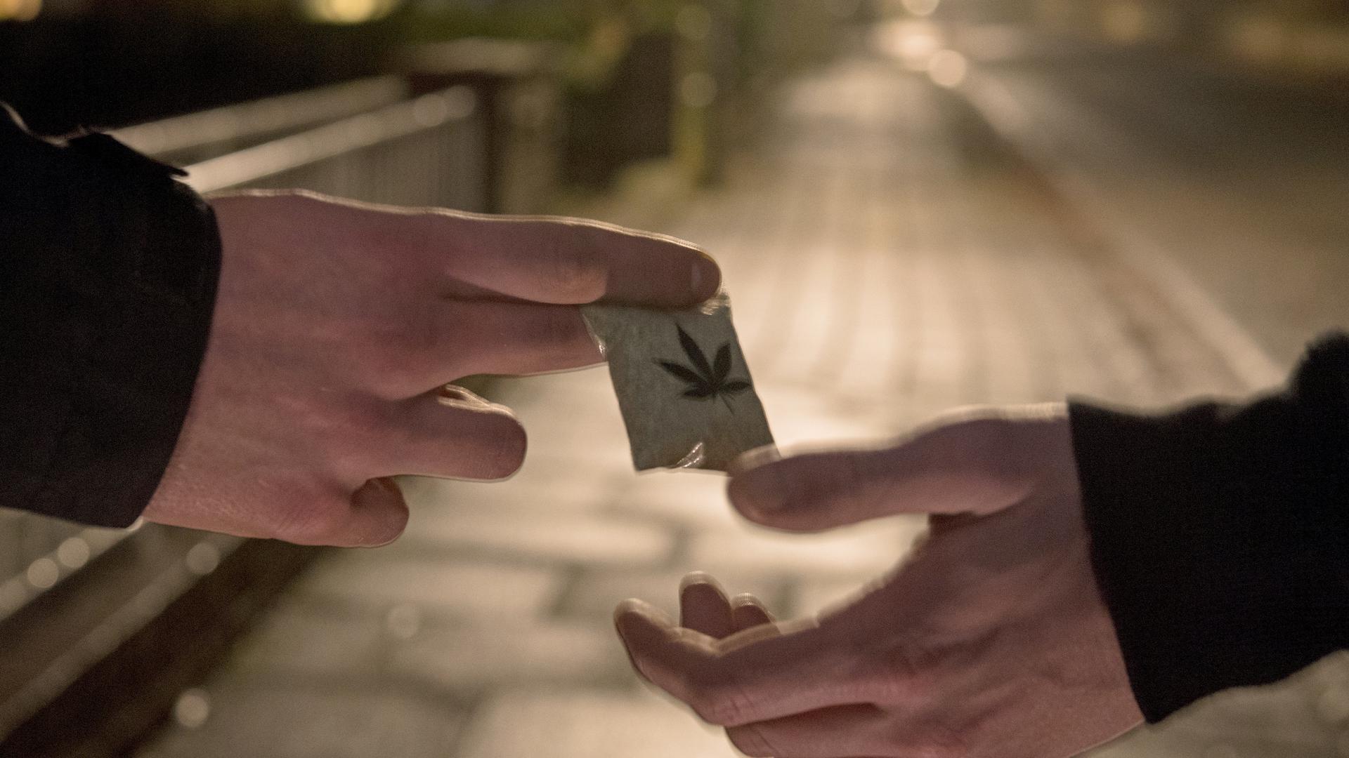ILLUSTRATION - Die gestellte Szene vom 13.12.2016 zeigt zwei Männer bei der Übergabe eines Tütchen Marihuanas auf einer Straße in Bremen. Die Bremer Polizei stellt am 14.12. eine neue _Regionale Eingreif- und Ermittlungsgruppe Straßendeal_ (REEG) vor. Mit der REEG soll der offene, sichtbare Drogenverkauf bekämpft werden. Foto: Ingo Wagner/dpa +++(c) dpa - Bildfunk+++ | Verwendung weltweit