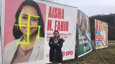 Lässt sich nicht unterkriegen: Aisha Fahir, Kandidatin der SPD aus dem Wahlkreis Ettlingen für die Landtagswahl, vor ihrem mit einem Hakenkreuz beschmierten Wahlplakat in Karlsbad.