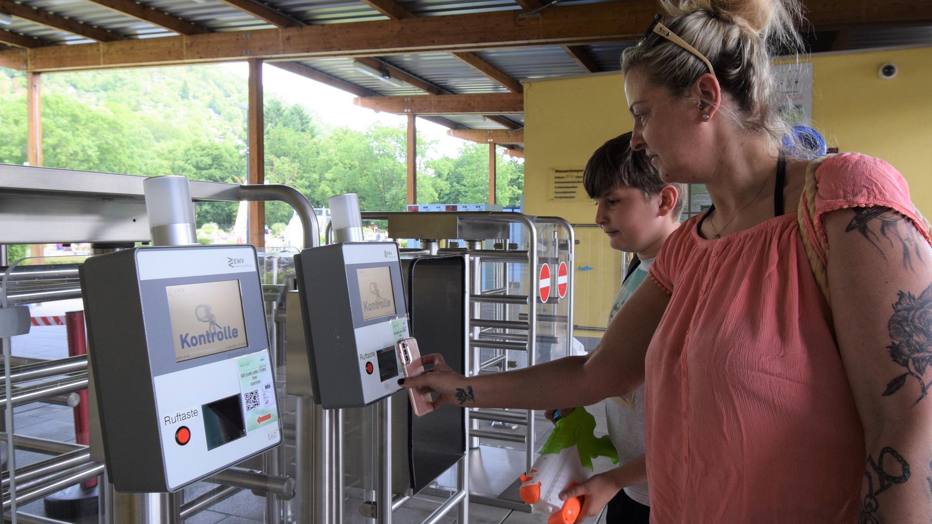Eine Besucherin des Ettlinger Freibades hält am Eingang ihr Smartphone vor einen QR-Code-Scanner.