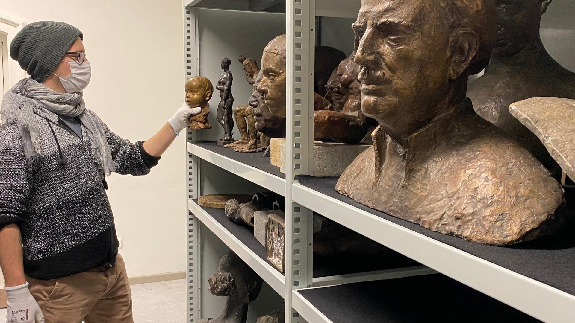 Man udn Skulpturen im Regal