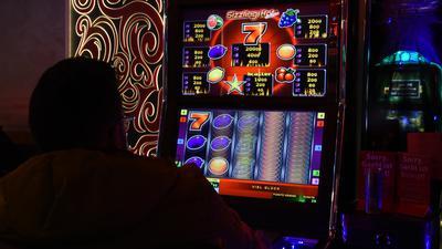 Eine Person sitzt vor einem Spielautomaten.