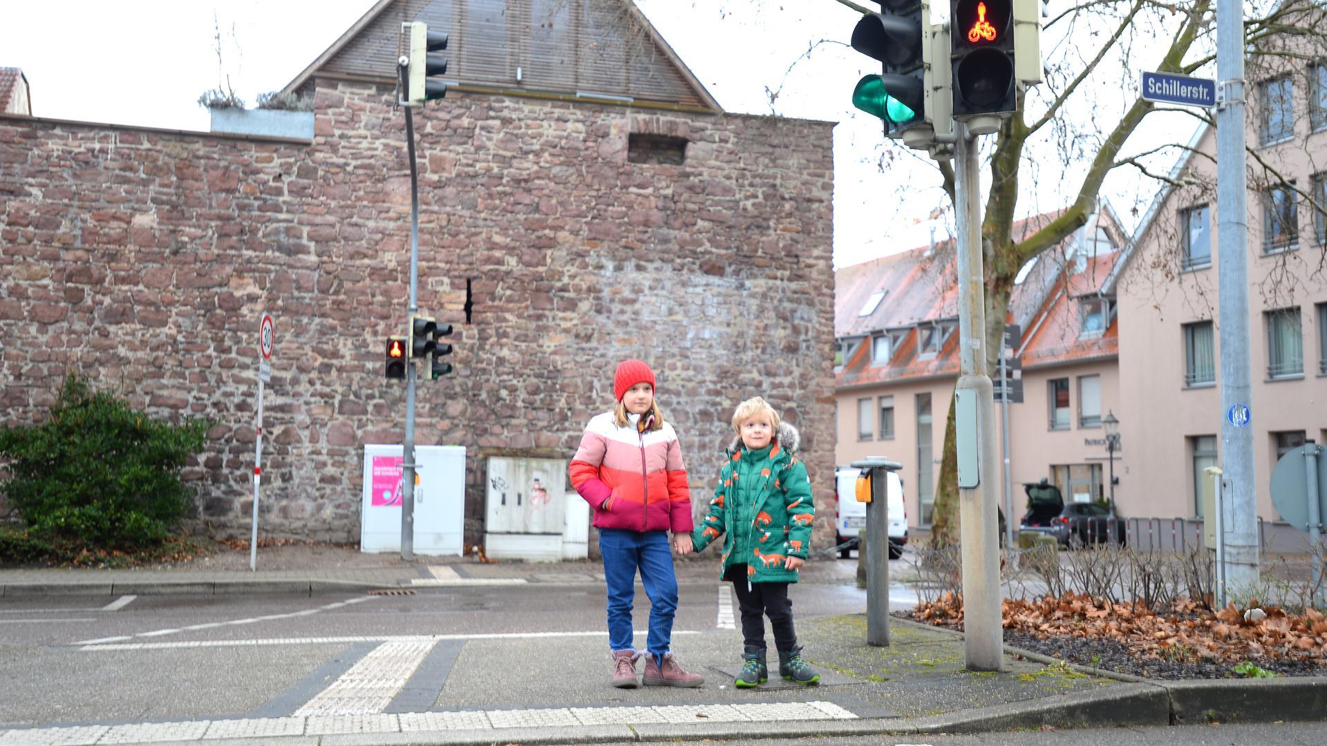 Zwei bildhübsche Kinder stehen an einer Ampel und warten auf grün.