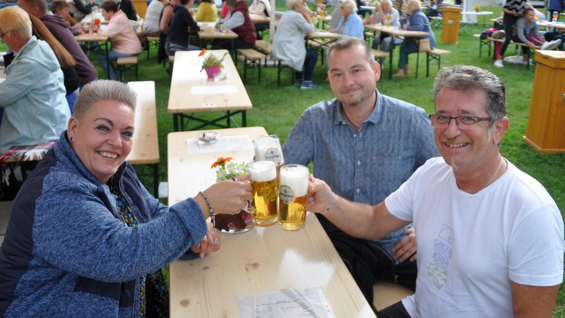 Susi Wirth, Reinhard Gräfinger und Thomas Steidl (von links) prosten sich zu. 2021 fiel das Ettlinger Marktfest wegen der Corona-Auflagen aus. Stattdessen errichteten Vereine in der Stadt mehrere Biergärten.