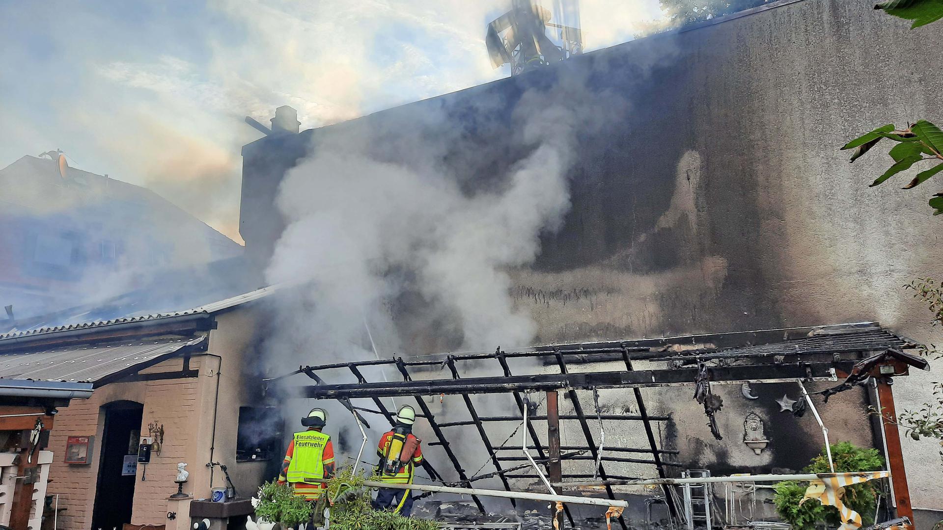 Feuerwehrleute, Rauch und Gebäude und abgebrannte Pergola