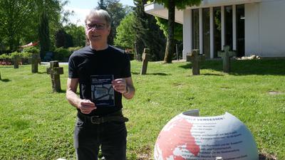 Mann mit Buch auf Friedhof