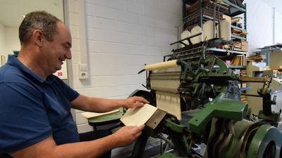 Buchbinder Santiago Sanchez-Ernst sitzt an der Fadenheftmaschine aus dem Jahr 1896.