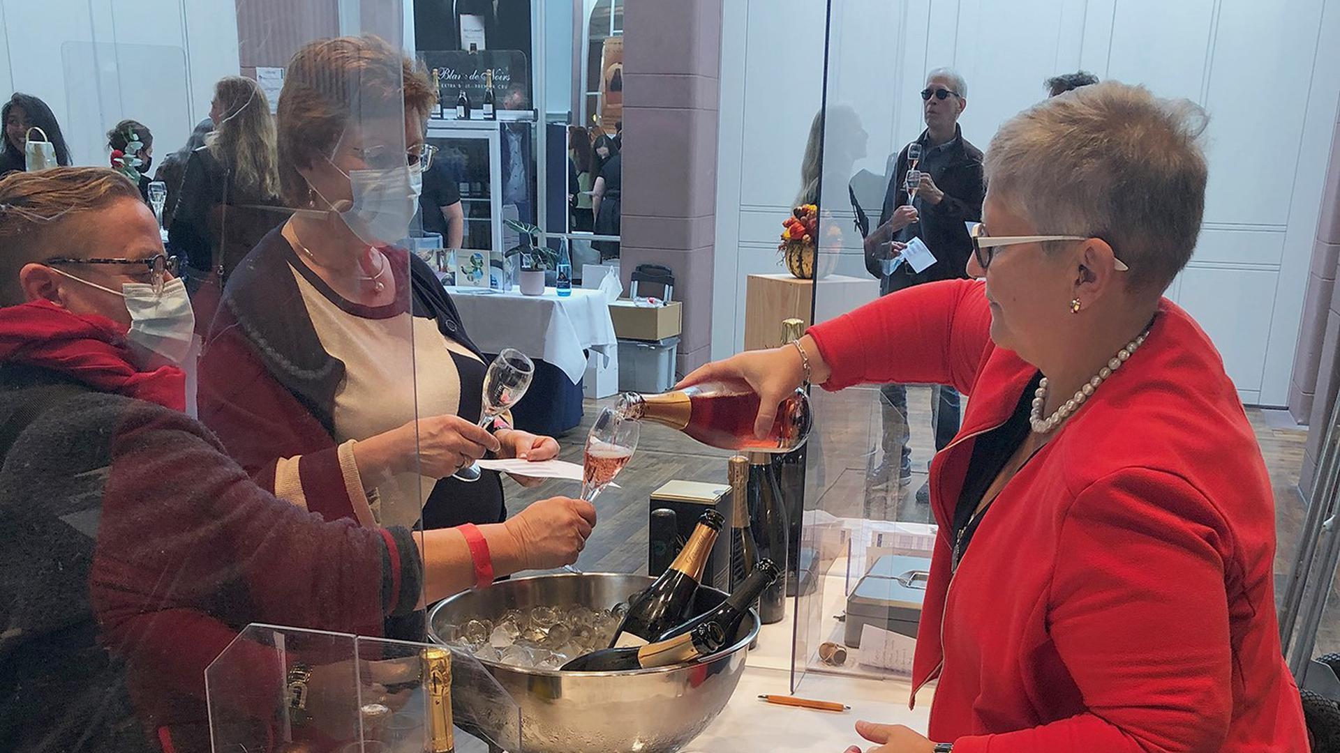 Frau in roter Jacke schenkt Frauen Champagner ein
