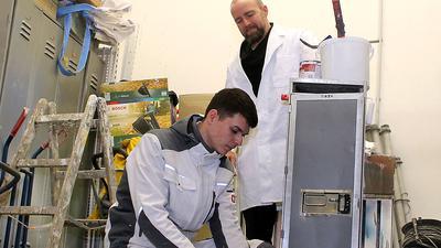Csernalabics schaut Lehrling Daniel über die Schulter beim Abkleben eines Objektes