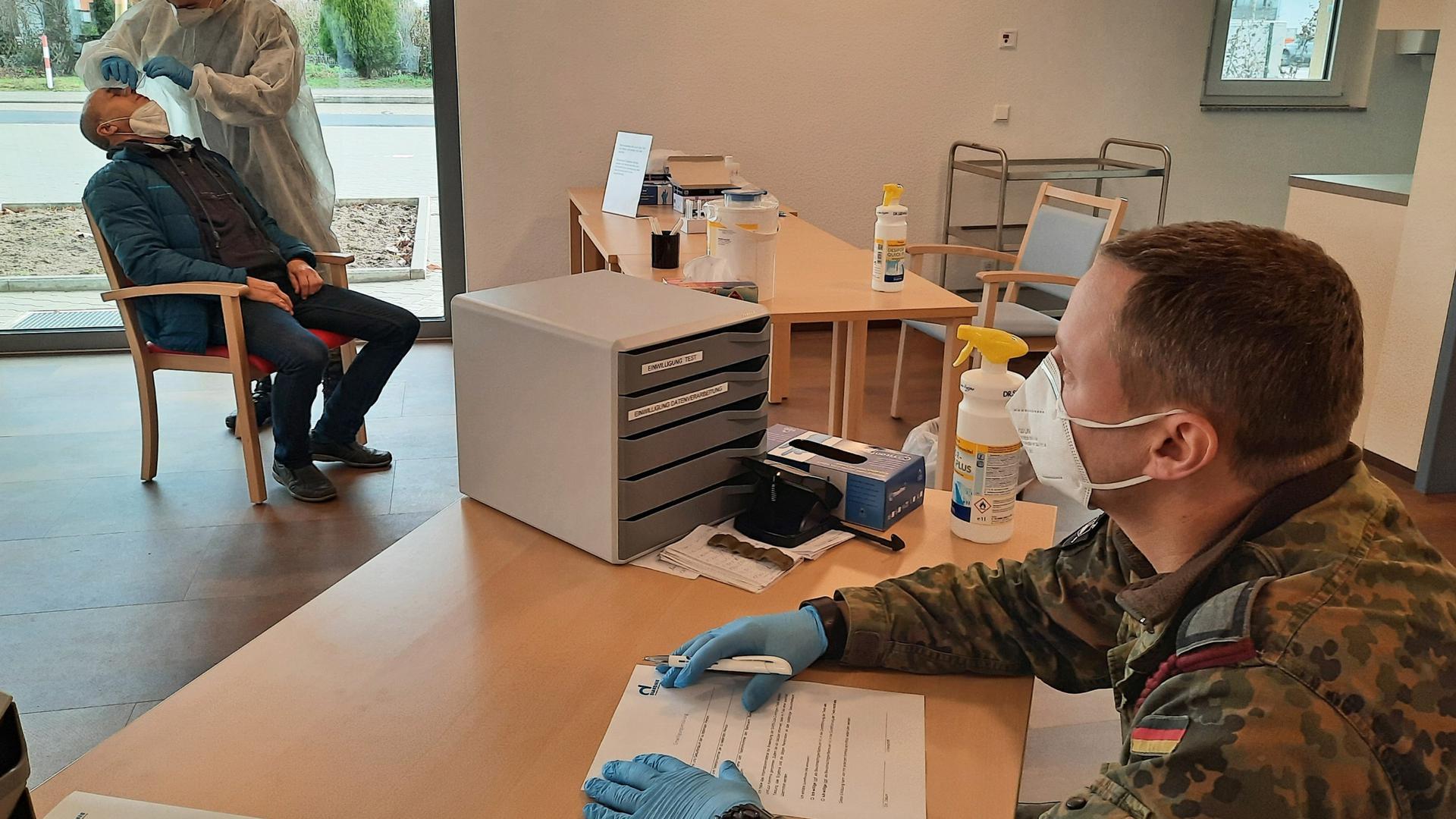Ein Mann am Schreibtisch und zwei Leute im Hintergrund, die einen Abstrich machen.