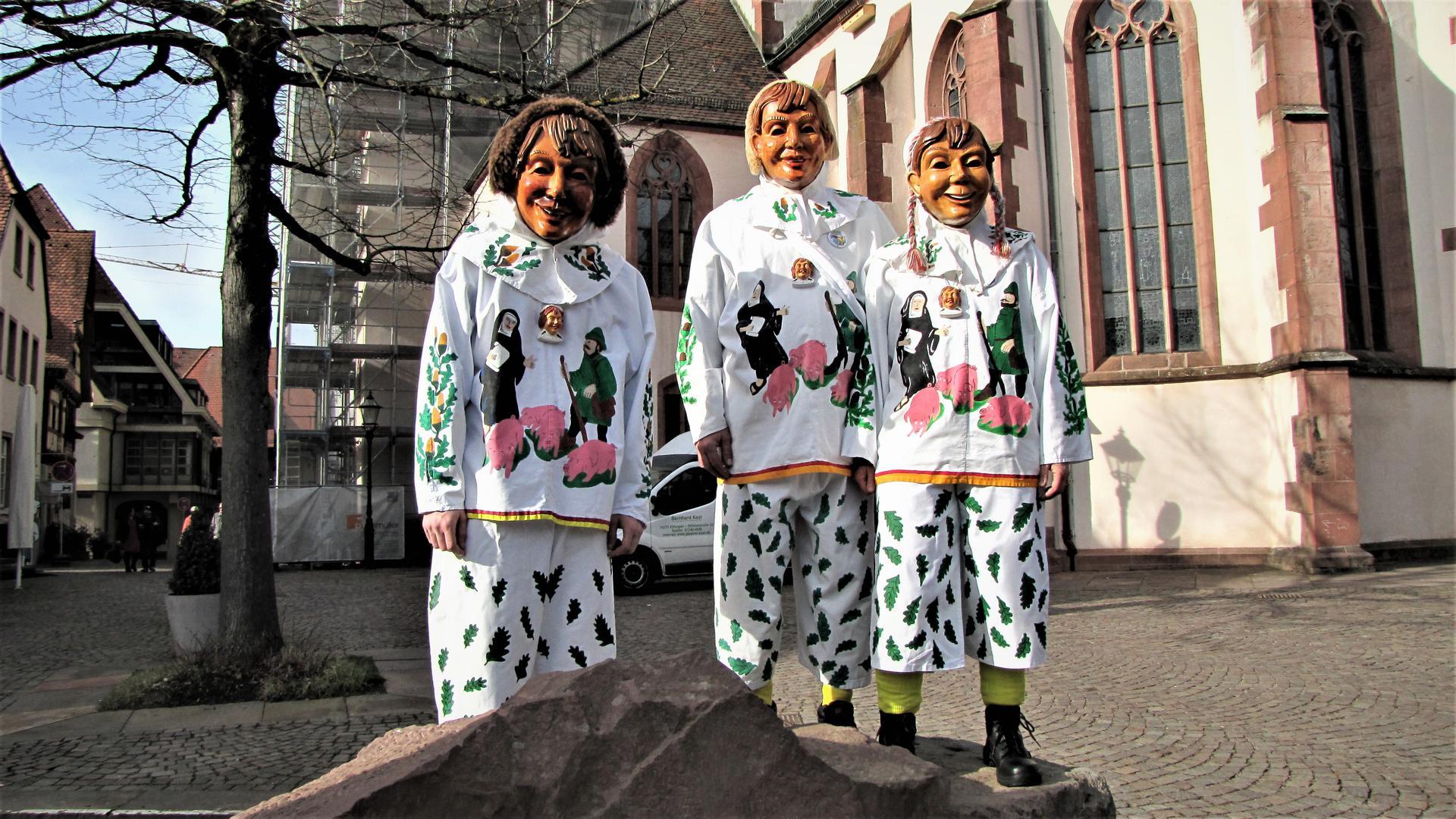 """Im traditionellen Häs, das auf einer alten Ettlinger Sage beruht, präsentieren sich Franziska, Christian und Bernhard Kast von der Gruppe """"Dohlenaze"""" des ECV bei der Martinskirche, wo es früher Dohlen gab."""