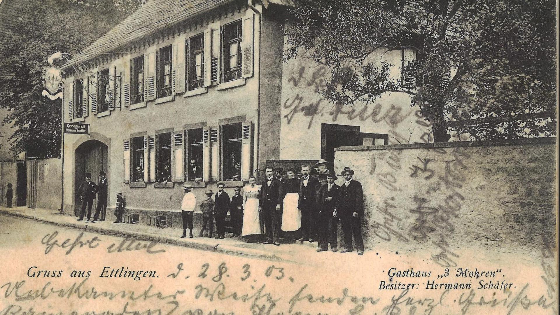 Menschen auf dem Bürgersteig vor einem alten Gasthaus