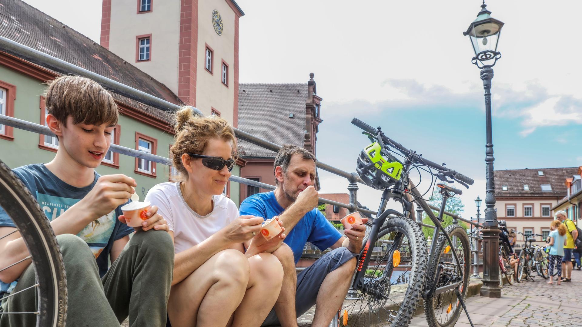 Ein Mann, eine Frau und ein Junge lehnen zwischen zwei Fahrrädern am Geländer an der Alb und löffeln Eiscreme.