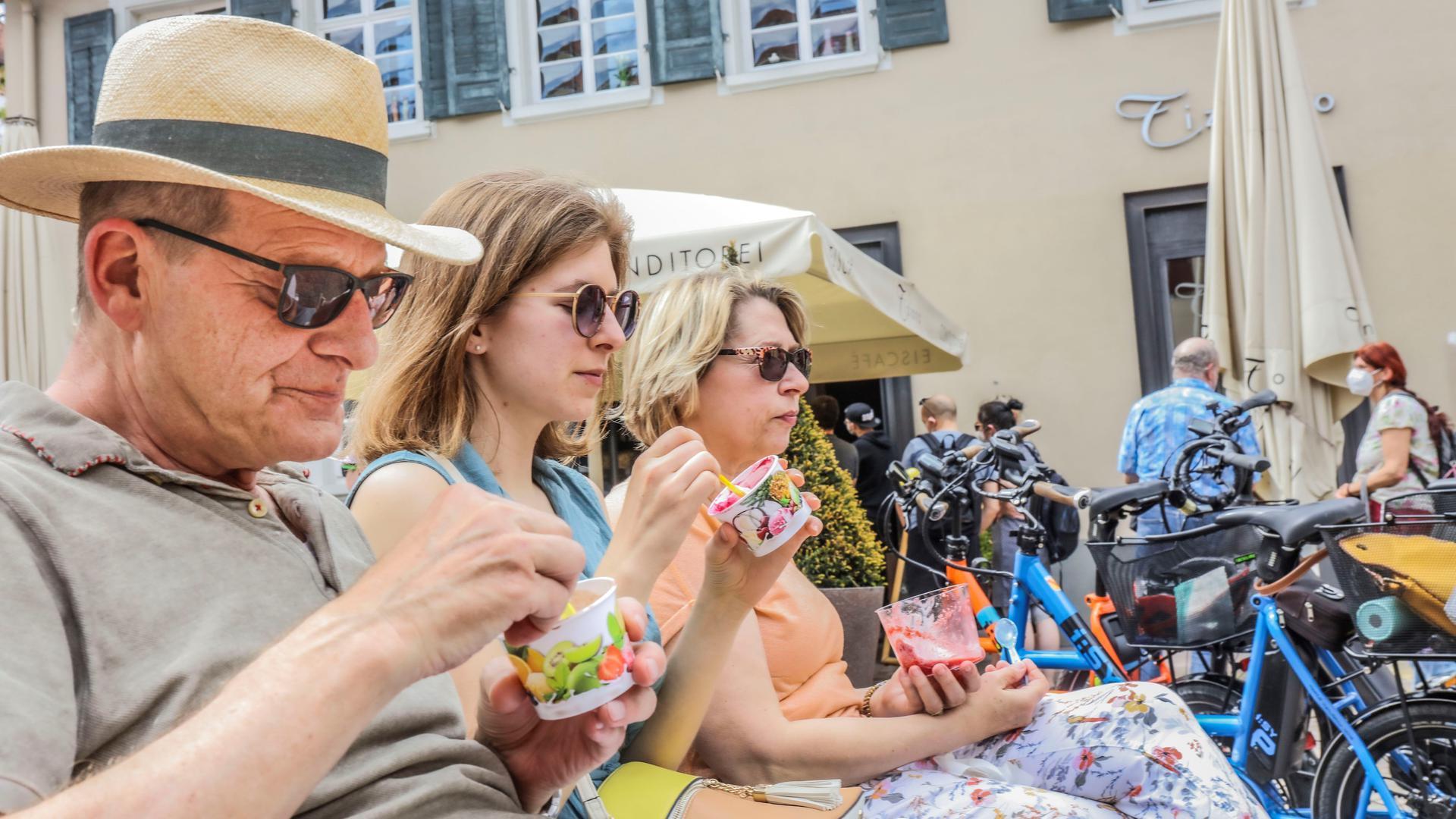 Ein Mann mit Hut und zwei Frauen mit Sonnenbrille löffeln Eis aus Eisbechern.