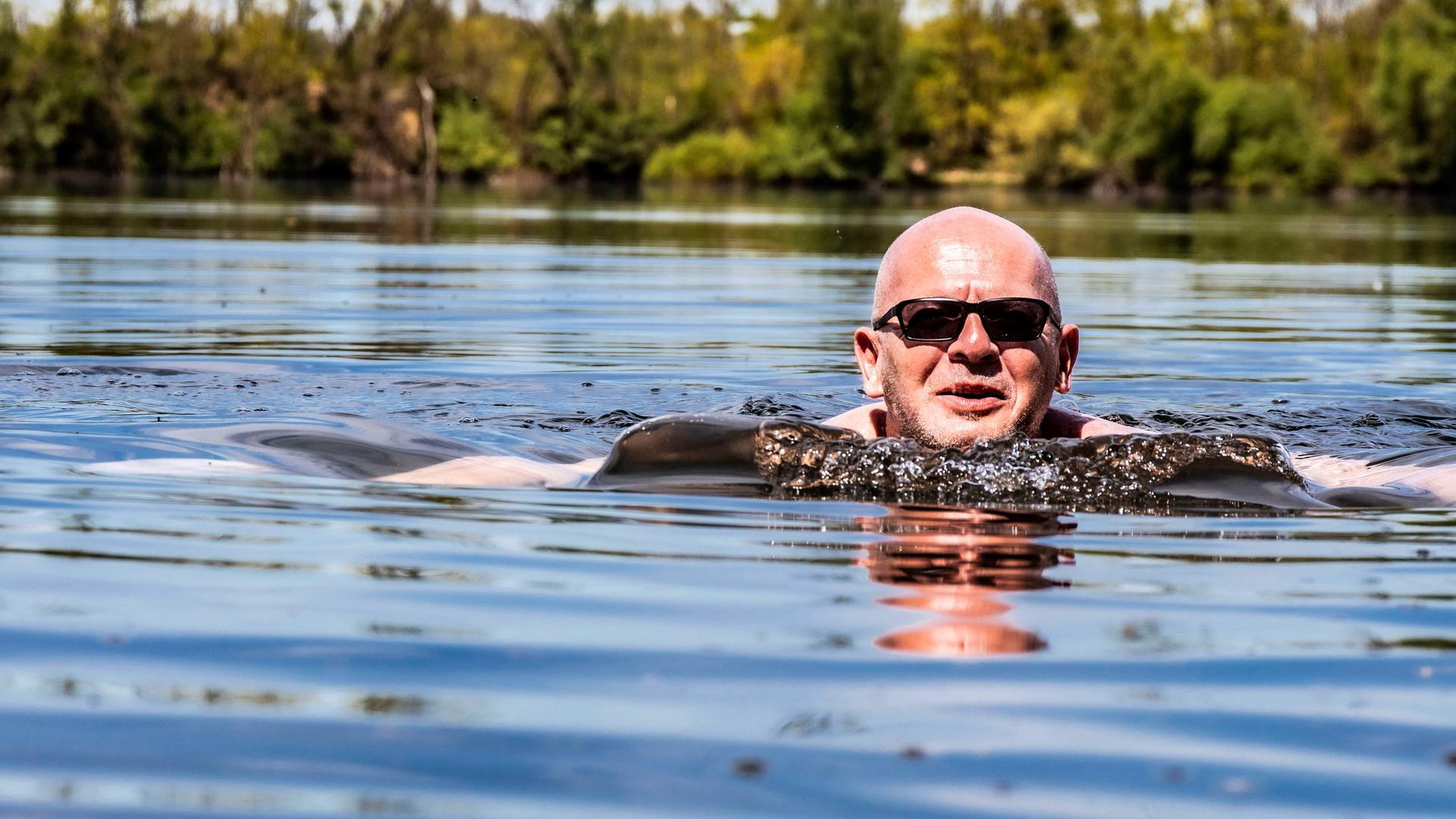 Ein Mann mit Glatze und Sonnenbrille schwimmt in einem Baggersee.