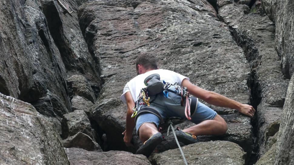 Mann hängt mit ausgebreiteten Armen in der Felswand