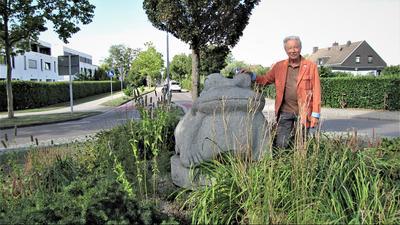 Der Frosch grüßt am Ortseingang: Der Bruchhausener Ortsvorsteher Wolfgang Noller neben der übergroßen steinernen Skulptur, die im Kreisverkehr auf der Landstraße von Ettlingen kommend steht.