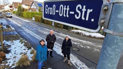 Drei Menschen bei einem Straßenschild