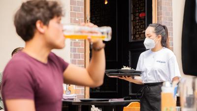 Thuy Nhi Nguyen, Kellnerin, trägt im Berliner Bezirk Prenzlauer Berg in einem Restaurant für asiatische Fusionsküche ein Tablett. +++ dpa-Bildfunk +++