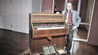 Mann steht vor einem alten Harmonium