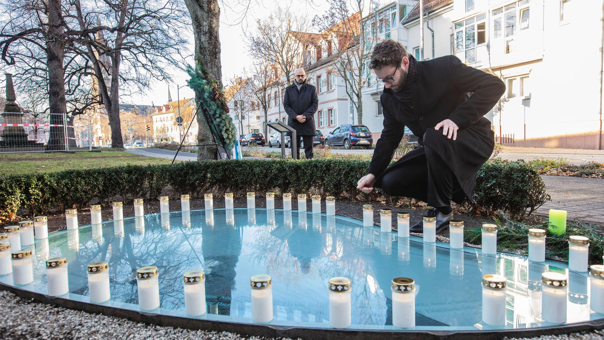 Bürgermeister Moritz Heidecker stellt eine Kerze auf eine Glasplatte am Mahnmal für die Ettlinger Juden.