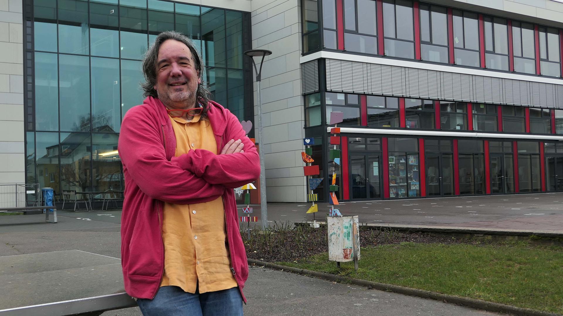 Mann mit roter Jacke vor einem Gebäude