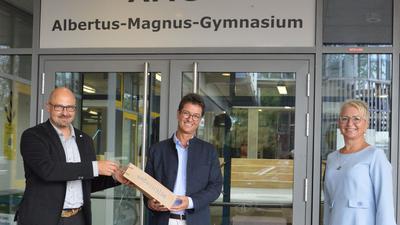 Ein Präsent für den Neuen: Oberbürgermeister Johannes Arnold (links) mit dem neuen AMG-Direktor Jochen Bischoff und der Bildungsamtleiterin Barbara Baron-Cipold.