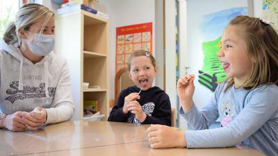 Die beiden Fünfjährigen Hannah (rechts) und Maya machen in der Ettlinger AWO-Kita Regenbogen II unter Aufsicht von Erzieherin Sarah Kienzle einen Corona-Selbsttest nach dem Lolli-Prinzip.