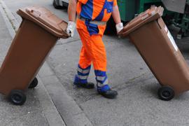 ARCHIV - Ein Mitarbeiter der Abfallwirtschaft und Stadtreinigung schiebt am 31.07.2012 in Freiburg (Baden-Württemberg) eine braune Tonne mit Biomüll zum Müllwagen. Foto: Patrick Seeger/dpa (Zu lsw «Biomüll lässt Gesamtabfallmenge steigen - «Tendenz stimmt»» vom 04.08.2014) +++(c) dpa - Bildfunk+++ ds