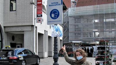 """Ruth Lingenfelser steht vor einem Schild mit der Aufschrift """"Achtung Maskenpflicht"""" in Ettlingen, vor ihr auf dem Boden liegt eine getragene Corona-Maske."""