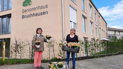 Frauen mit Blumen vor Haus