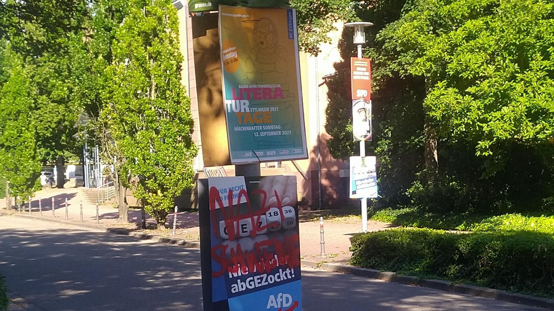 An einem Laternenmast hängen drei Plakate. Eines wirbt für die Literaturtage in Ettlingen. Oben hängt ein Wahlplakat der Grünen, unten das der AfD, das beschmiert worden ist.