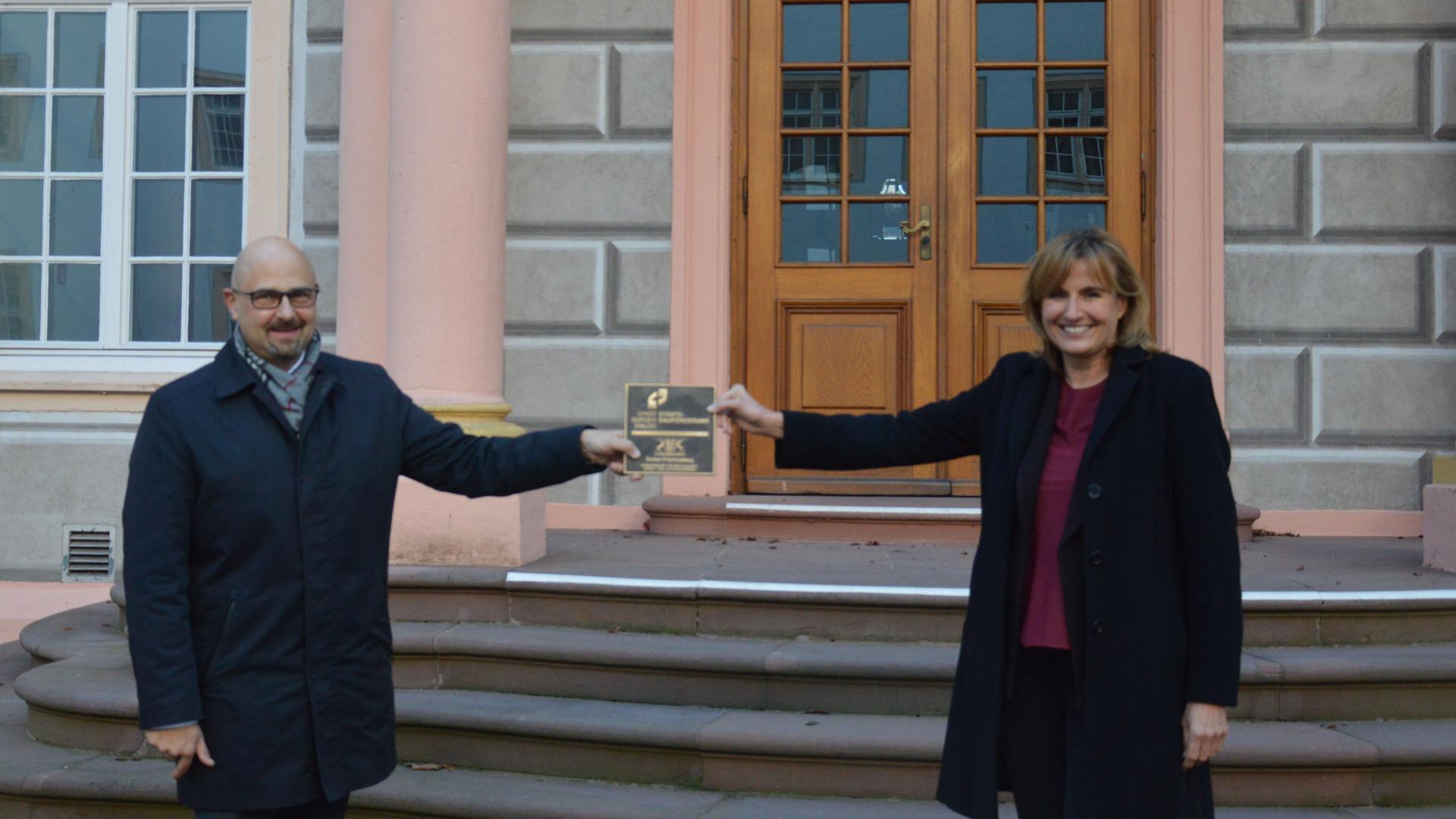 Zwei Leute mit Tafel vor Gebäude