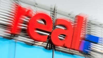 Das Logo von real ist am 30.03.2016 in Düsseldorf (Nordrhein-Westfalen) über dem Eingang zum real-Markt zu sehen (Aufnahme mit Zoomeffekt). Die beiden wichtigsten Geschäftsbereiche des Konzerns Metro - das Großhandelsgeschäft und die Elektroniksparte Media Saturn - sollen künftig als selbstständige Unternehmen geführt werden. Foto: Monika Skolimowska/dpa (zu dpa «Handelskonzern Metro will sich aufspalten» vom 30.03.2016) ++ +++ dpa-Bildfunk +++