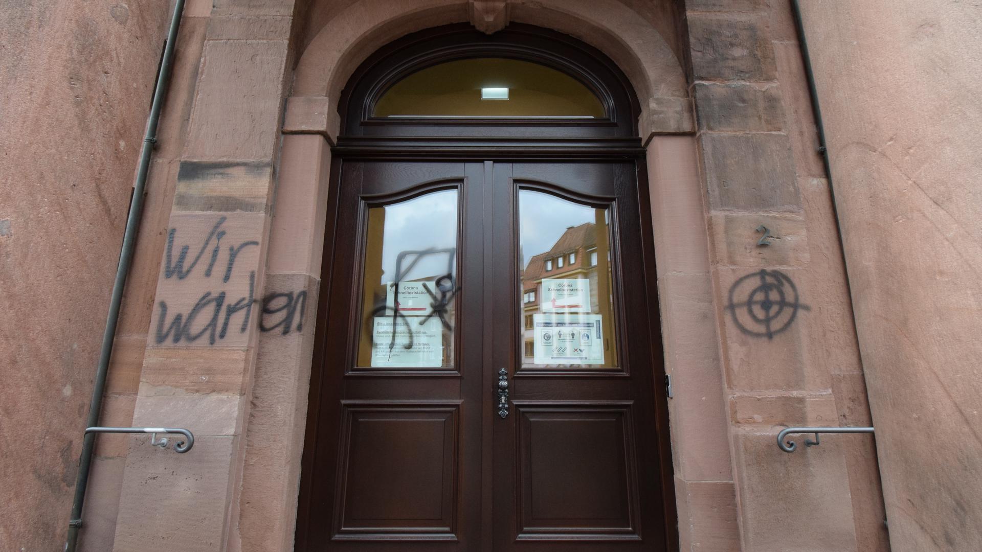 """Drohung am Rathaus: Ein Galgenmännchen mit der Drohung """"Wir warten"""" und eine Zielscheibe hat der 37-Jährige im Eingangsbereich an Wand und Tür gesprüht."""