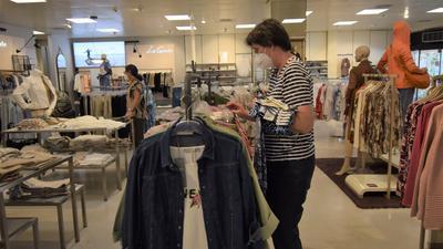 Andrea Metzger-Adolf schaut sich die Blusen und T-Shirt an einer Kleiderstange im Modehaus Streit in Ettlingen an.