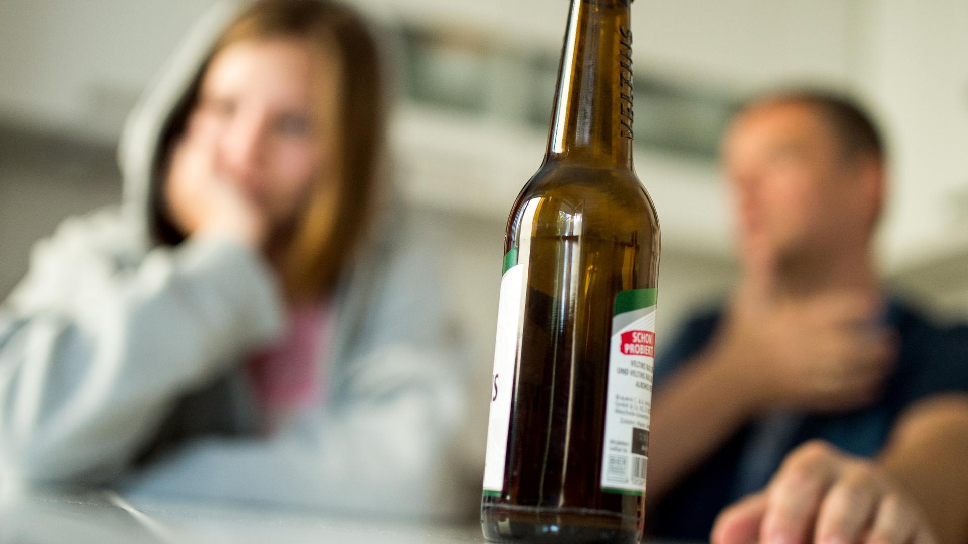 Ein Mädchen streitet mit ihrem Vater, während im Vordergrund eine Bierflasche steht. (Symbolbild)