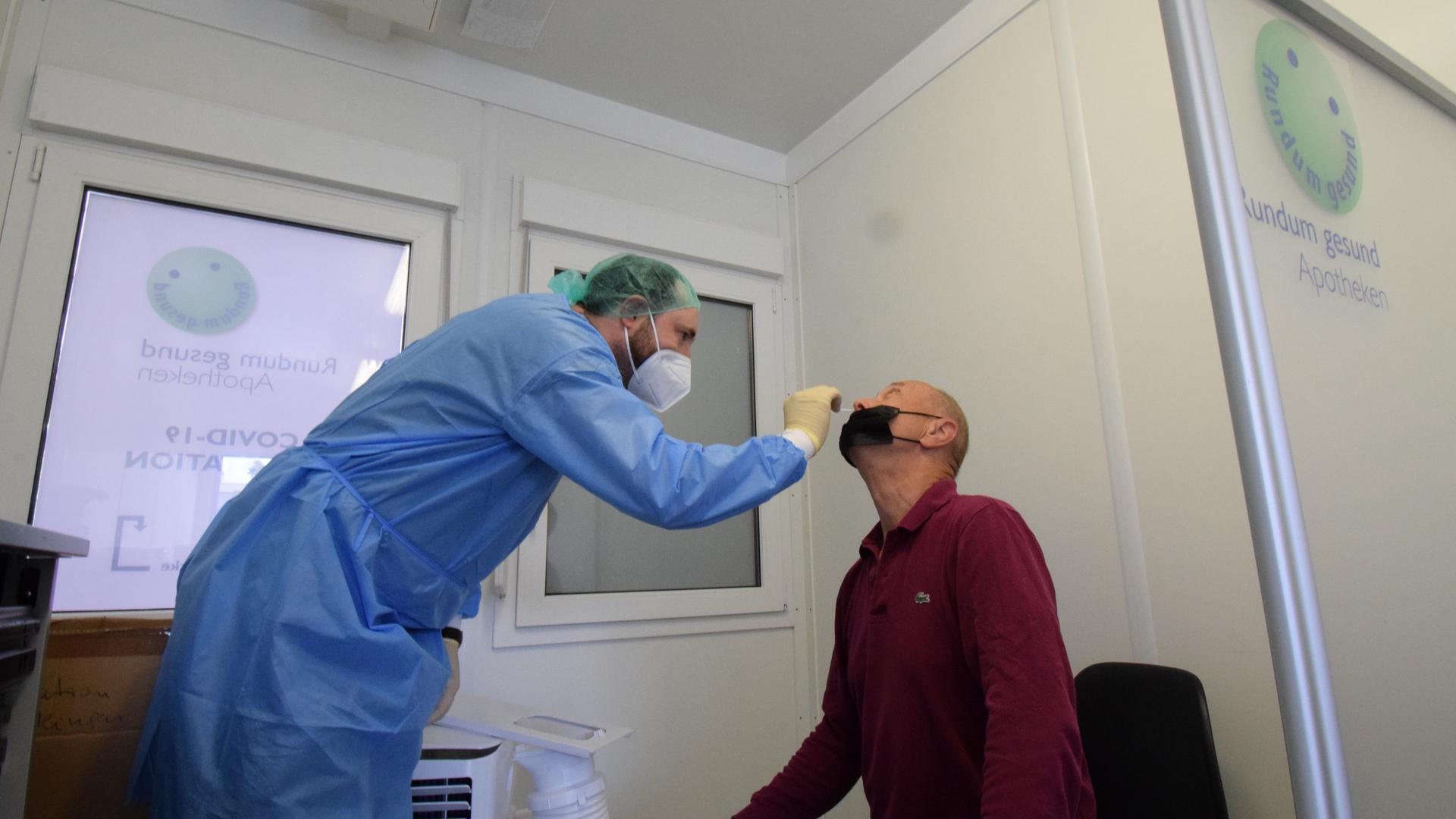 Ein Mitarbeiter der Corona-Teststation am Real-Markt in Ettlingen nimmt einen Nasenabstrich bei einem Besucher.