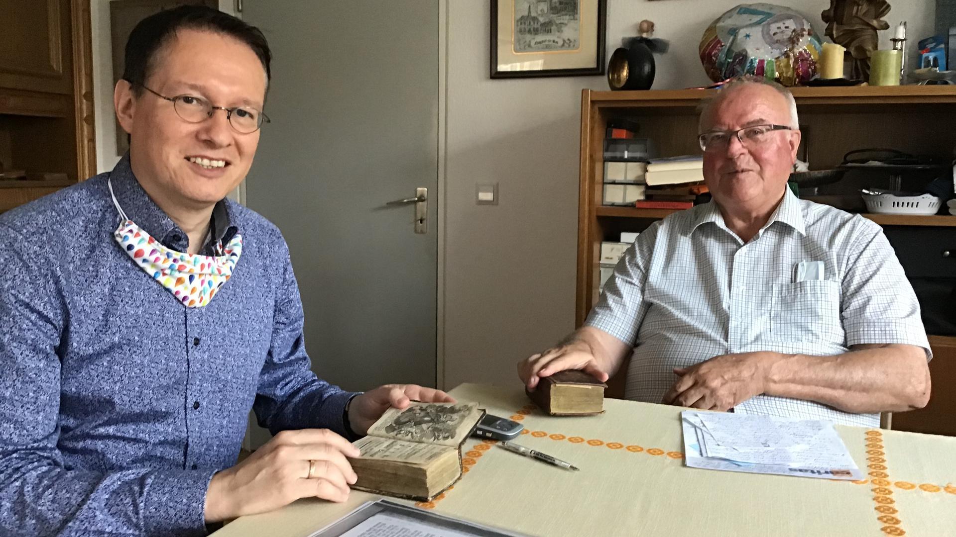 Zwei Männer am Tisch mit zwei alten Büchern