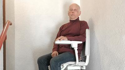 Michael Graßl sitzt in seinem Treppenlift.