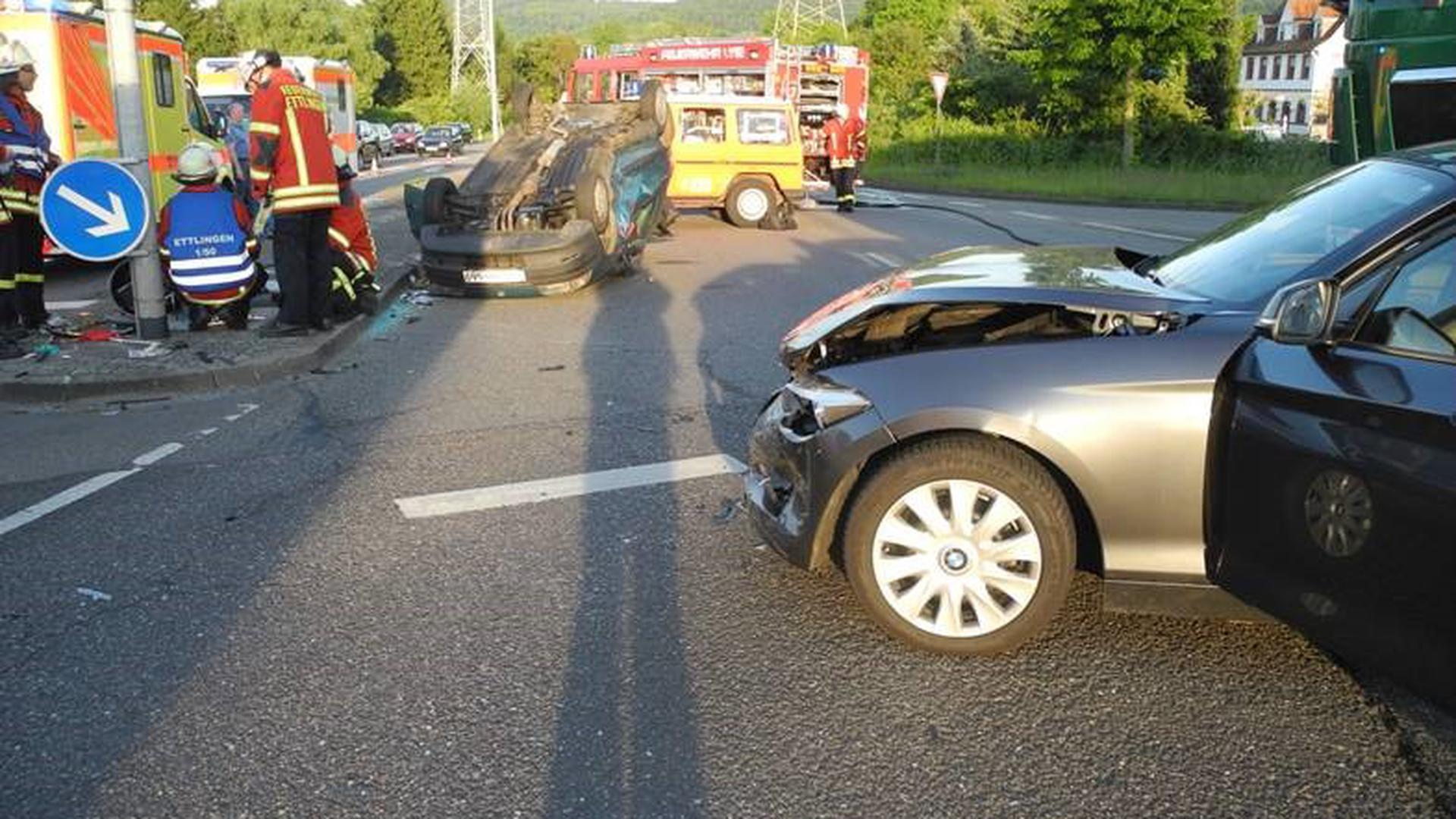 Auto auf Dach, Einsatzkräfte und ein leicht demoliertes Fahrzeug im Vordergrund.