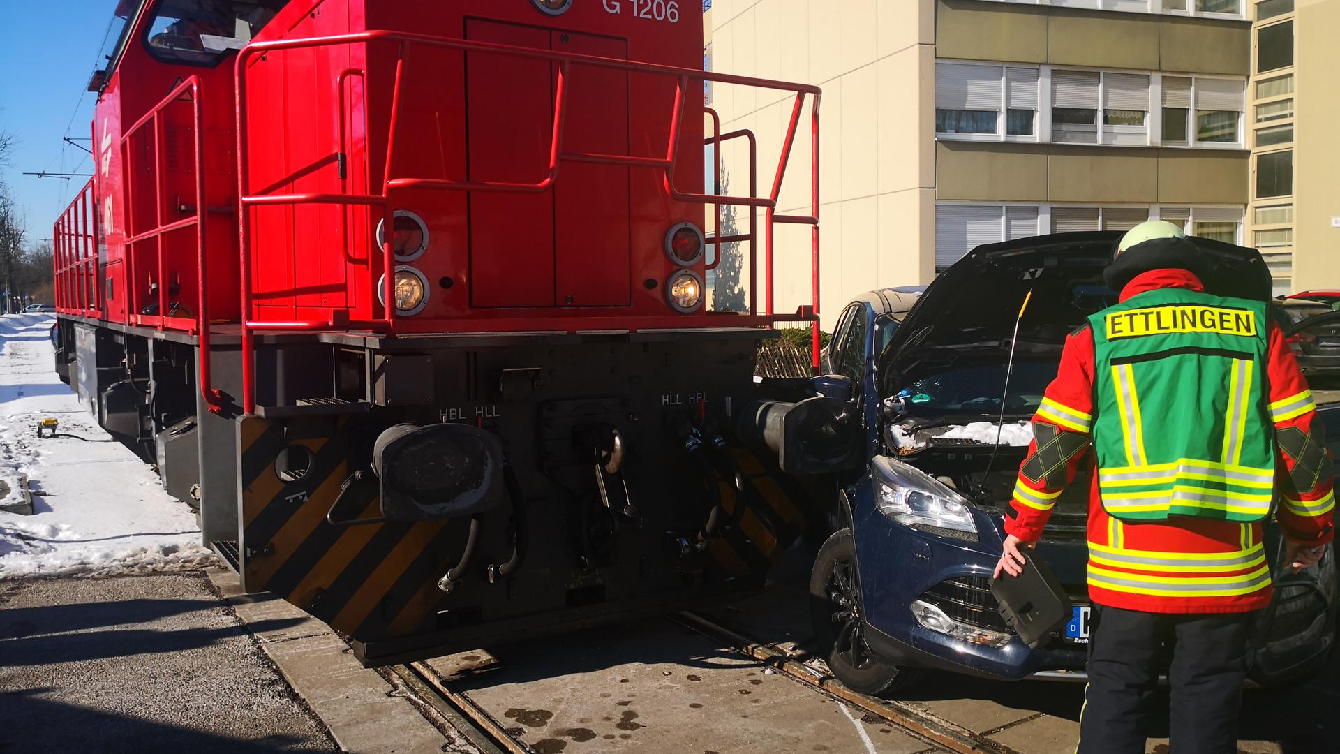 Eine rote Rangierlok steht auf den Gleisen, ein dunkelblaues Auto ist auf der Beifahrerseite mit der Lok zusammengestoßen. Ein Feuerwehrmann steht mit dem Rücken zum Betrachter vor dem Pkw.