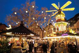 Besucher stehen auf dem Weihnachtsmarkt in Ettlingen, dem Sternlesmarkt, vor den Ständen und der Glühwein-Pyramide.