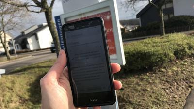 Ein Handy mit der Ettlinger Wikipedia-Seite vor dem Ortseingang des Stadtteils Schöllbronn.
